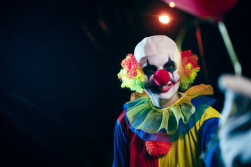Photo of clown with red balloon at night on street