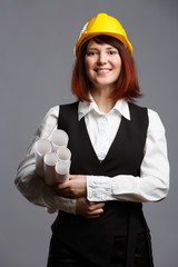 Picture of woman builder in yellow helmet with drawings in rolls