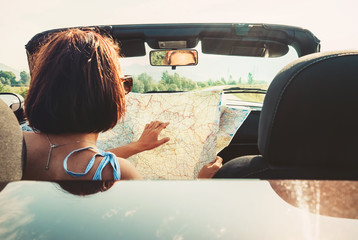 Woman reads roads map sitting in cabriolet car
