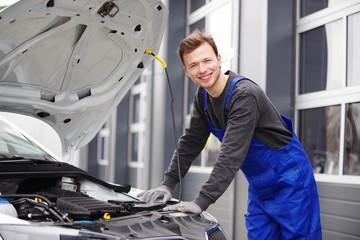 Automechaniker sympathisch lächelnd inspiziert einen Motor