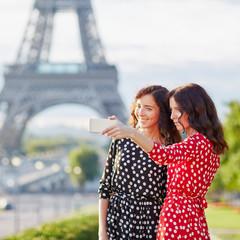 twin sisters taking selfie in front of Eiffel Tower