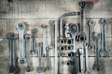 set of metal wrench rests on wooden background abstraction