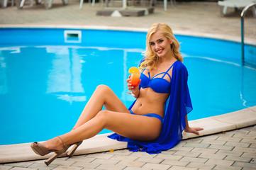 fashion outdoor photo of beautiful sensual woman wearing elegant bikini, posing beside swimming pool with cocktail