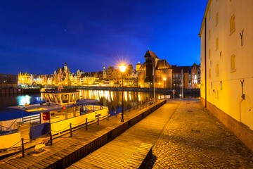 Architecture of the old town in Gdansk over Motlawa river at night, Poland