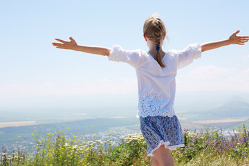 Cute happy  child in white blouse on a rock with raised hands and looking to a valley below