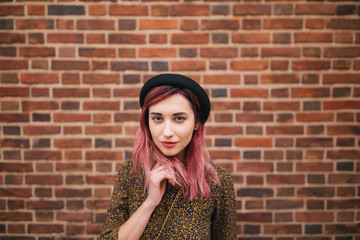 beautiful stylish girl with pink hair in hat posing at wall