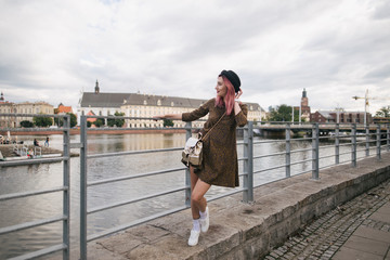 stylish girl in trendy dress and hat walking at river in Wroclaw, Poland