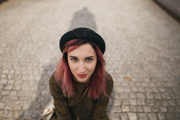 young girl with pink hair in trendy hat sitting on pavement in city