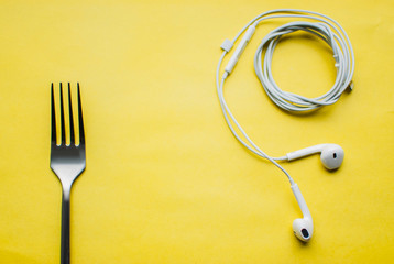 Music for dessert. Top view of a fork and white headphones against yellow background