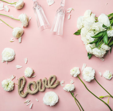 Saint Valentines Day frame and background. Flat-lay of white ranunculus flowers, champaign glasses and word love over light pink background, top view, copy space. Greeting card or wedding invitation