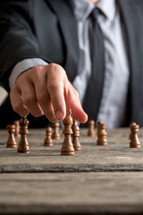 Businessman playing a game of chess on an old wooden table