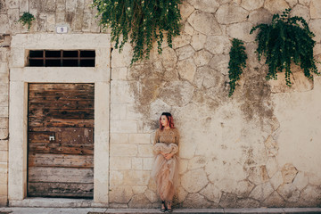 elegant girl in glamorous dress posing near shabby wall with plants