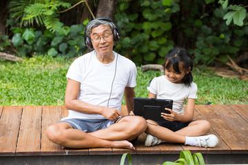 Happy asian senior man Headphones Listening Music with grandchild in park