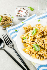 Vegan dinner. Farfalle pasta with pesto sauce and basil leaves on white plate, grey stone background, copy space