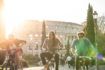 Three young friends tourists riding bikes in colle oppio park in front of colosseum on road with trees at sunset in Rome