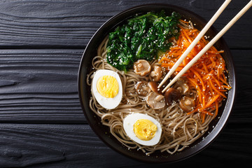 Asian Soba soup with vegetables, mushrooms, egg and sesame seeds close up. Horizontal top view