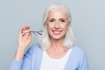 Old, charming, pretty woman showing glasses for sight, senior, people health care, standing over grey background
