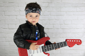 little child with rock star costume playing a guitar