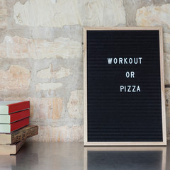 "letterboard with ""workout or pizza"", pizza boxes and copyspace"