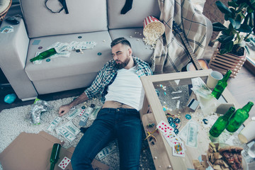 After party consequences. Top view above photo of drunk bearded wearing checkered shirt and jeans, he is sleeping on the floor and surrounded by money, popcorn, leftovers and mess