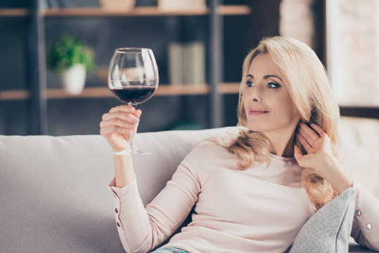 Portrait of pretty, charming, attractive, stylish connoisseur woman sitting on couch having raised glass with red wine in hand, examine, taste beverage