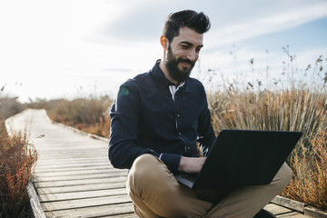 Content man enjoying laptop in nature
