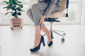 Concept of getting varicose because of wearing high heels. Cropped close up photo of woman's legs wearing grey trousers and black modern shoes, hand is touching a leg