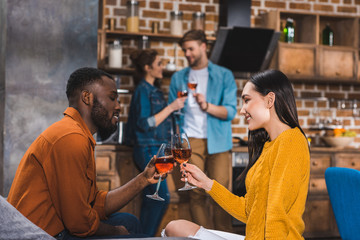 side view of young multiethnic couple drinking wine while friends standing behind