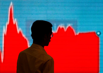 A man walks past a screen displaying news of markets update inside the Bombay Stock Exchange (BSE) building in Mumbai