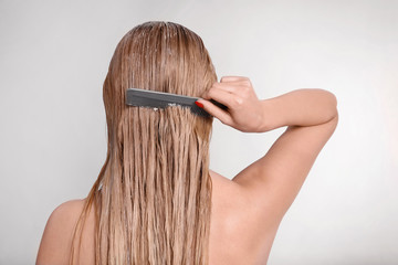 Young woman combing hair covered with mask on light background