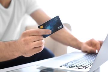 Man with credit card and laptop, closeup