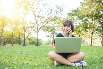 Cute asian woman smiles and talking on mobile phone while sitting in park spring day. Asian woman using on smart phone and laptop with feeling relax and smiley face. Lifestyle and technology concepts.