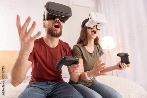7666ba99598 Energetic optimistic enthusiastic couple holding joysticks while using VR  glasses and shouting