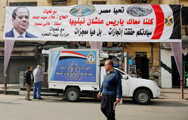 Egyptians buy subsidized food in a vehicle contributed by the Ministry of Defence and Military Production of the Egyptian Armed Forces around a huge banner for Egypt's President Abdel Fattah al-Sisi in Cairo