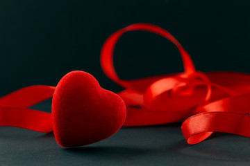 Valentine's Day. Red heart and red ribbon, as a symbol of the holiday.