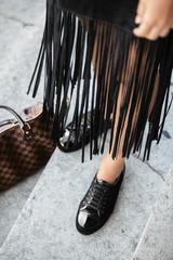 Détail des chaussures et de la jupe d'une blogger avec son sac à main