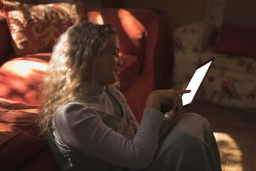 Mature woman sitting on ground and using her tablet