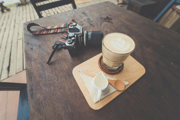 Cup of coffee with  camera on wooden table