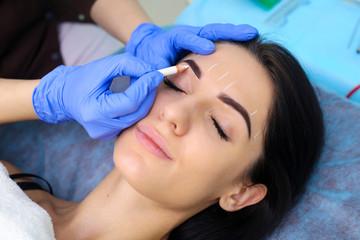 Young beautiful woman making permanent makeup in cosmetology salon.