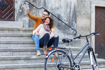 Young smiling couple using mobile phone while sitting on the stairs.