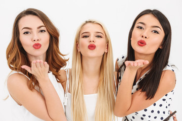 Three young cute girls friends blowing kisses.