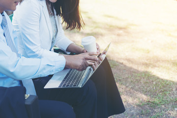 Picture of stylish mature businessman and businesswomen  sitting on a park bench with his digital tablet. Businessman and women having work discussion in the park. Man, women having free time in park.