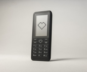 Mobile phone sending love heart. Portable communication device. Valentines day text message