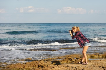 A young woman taking pictures at a beach; wearing shorts and plaid shirt; blonde, pony tail. Standing on sea rocks; sea, sky, clouds in background.