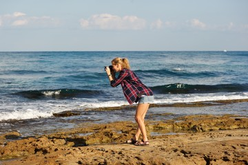 A young blonde woman wearing short shorts and plaid shirt taking pictures on a beach. Standing on sea rocks; sea, sky, clouds in background.