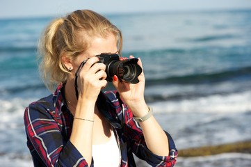 A young woman taking pictures on a beach; wearing white top and plaid shirt; ponytail. Seascape in the background.