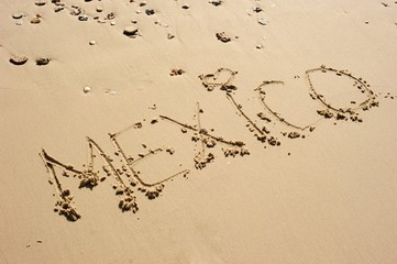 Mexico, with a hear shape for a dot over i, written in the sand. Some seashells and pebble laying around.