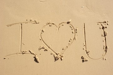 """I love you"" written in the sand with the heart shape drawn instead of the word ""love"". Clear and simple, smooth sandy background."