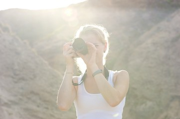 A young woman taking pictures; face hidden behind camera; bright sun and hills behind her.
