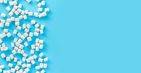 Marshmallows on blue background with copyspace. Flat lay or top view. Background or texture of colorful mini marshmallows. Winter food background concept.
